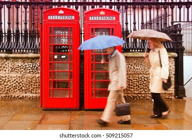 London, UK - red telephone boxes in wet rainy weather. Wet pedestrians with umbrellas. Filtered colors.