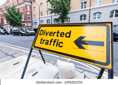 London, UK road closed closeup roadblock diverted traffic yellow sign text in city with street and cars traffic in Pimlico