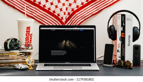 LONDON, UK - SEP 13, 2018: Creative room table with Safari Browser on MacBook Pro laptop showcasing Apple Computers website latest iPhone Xs smartphone with 4k video and stereo playback