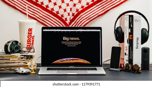 LONDON, UK - SEP 13, 2018: Creative room table with Safari Browser open on MacBook Pro laptop showcasing Apple Computers website latest iPhone X with big news on screen