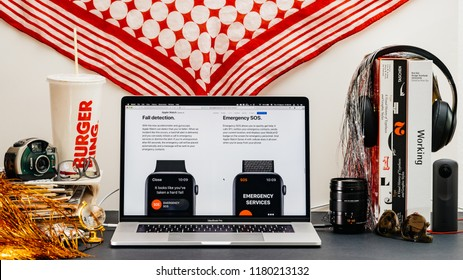LONDON, UK - SEP 13, 2018: Creative room table with Safari Browser on MacBook Pro laptop showcasing Apple Computers website latest Apple Watch series 4 with fall detection emergency sos