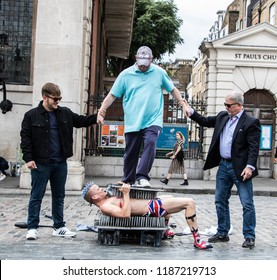 London, UK - Sept 22, 2018: Shirtless daredevil performer with union jack underwear performing a dangerous stunt for a crowd in Covent Garden