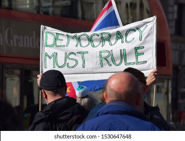 """London, UK. Sept 25 2019. A pro Brexit, protest sign held by demonstrators in Westminster outside the British Houses of Parliament that reads """"Democracy Must Rule"""""""