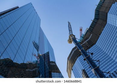 London, UK - September 02, 2018: Modern building under construction at a bright sunny day on the blue sky background. Reflection of tower cranes on windows mirror. Low angle view