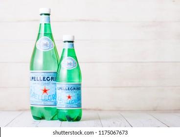 LONDON, UK - SEPTEMBER 03, 2018: Plastic Bottles of San Pellegrino mineral water on wood. San Pellegrino is an Italian brand of mineral water produced and bottled by Nestle