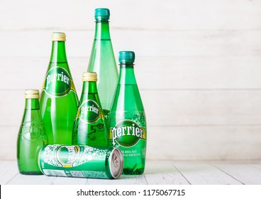 LONDON, UK - SEPTEMBER 03, 2018: Bottles and aluminium tin of Perrier sparkling water on wooden background. Perrier is a French brand of natural bottled mineral water sold worldwide.