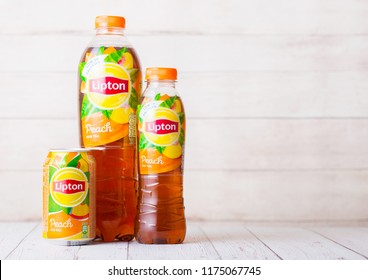 LONDON, UK - SEPTEMBER 03, 2018: Aluminium can and plastic bottles of Lipton Ice Tea with peach flavour on wood.