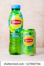 LONDON, UK - SEPTEMBER 03, 2018: Aluminium can and plastic bottle of Lipton Ice Green Tea on wood.