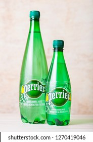 LONDON, UK - SEPTEMBER 03, 2018: Bottles of Perrier sparkling water on wooden background. Perrier is a French brand of natural bottled mineral water sold worldwide.