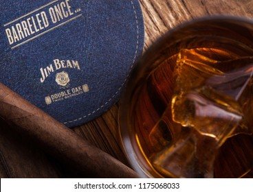 LONDON, UK - SEPTEMBER 04, 2018: Glass of Jim Beam Bourbon whiskey with original coaster and cigar on wooden board.