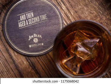 LONDON, UK - SEPTEMBER 04, 2018: Glass of Jim Beam Bourbon whiskey with original coaster on wooden board.