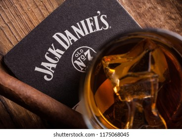 LONDON, UK - SEPTEMBER 04, 2018: Glass of Jack Daniel's whiskey with original coaster and cigar on wooden board.