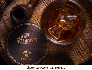 LONDON, UK - SEPTEMBER 04, 2018: Glass of Jim Beam Bourbon whiskey with original coaster and vintage smoking pipe on wooden board.