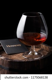 LONDON, UK - SEPTEMBER 04, 2018: Glass of Hennessy Cognac with original coaster on top of wood.