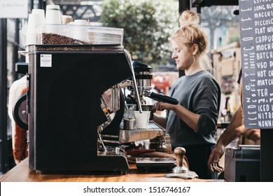 London, UK - September 07, 2019: Coffee machine at Climpson & Sons with staff behind inside Spitalfields Market, one of the finest Victorian markets in London with fashion, antiques and food stalls.