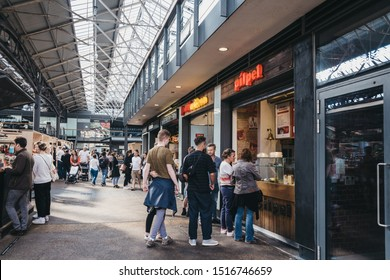 London, UK - September 07, 2019: People ordering food from food stalls inside Spitalfields Market, one of the finest Victorian Market Halls in London with fashion, antiques and food stalls