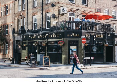 London, UK - September 07, 2019: Facade of The Black Horse pub in Aldgate, Spitalfields, a trendy area of Londons East End that is home to an array of markets, bars and restaurants. Man walking by.