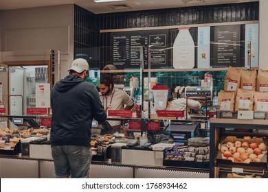 London, UK - September 07, 2019: Single customer ordering food from a counter inside Pret a Manger, separated from barista by protective plastic screen. The changes were introduced due to Coronavirus.