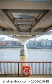 London, UK / September 1, 2020 -Orange Emergency Floatation Device Along the Thames Path in the UK