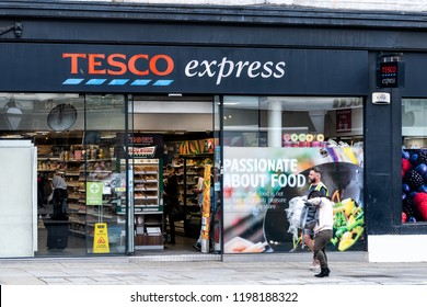 London, UK - September 12, 2018: Neighborhood local store Tesco Express grocery shopping storefront facade exterior entrance with red sign, people walking