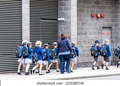 London, UK - September 12, 2018: Group of many school children on field trip walking on sidewalk street with uniforms, backpacks and teachers guardians in Westminster, Pimlico