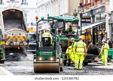 London, UK - September 12, 2018: Construction workers with neon yellow green uniforms vests clothing, hot black wet tar and asphalt, bitumen in city site