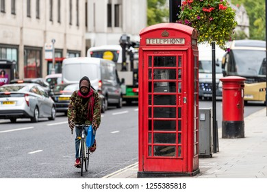 London, UK - September 12, 2018: Man pedestrian riding bicycle in traffic on street road in Pimlico district neighborhood area by vintage retro red telephone booth