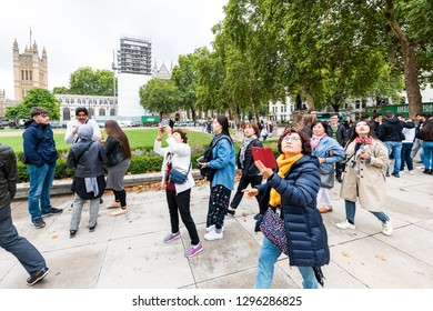 London, UK - September 12, 2018: Westminster area with Parliament Square Garden and crowd group of many people asian tourists walking motion during day