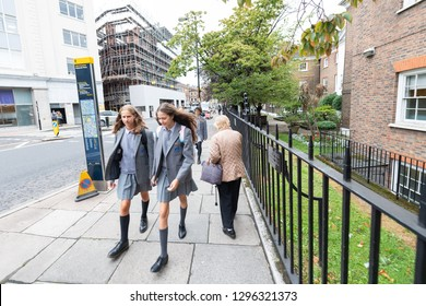 London, UK - September 12, 2018: Two girls school children walking on sidewalk street with uniforms in Westminster urban area