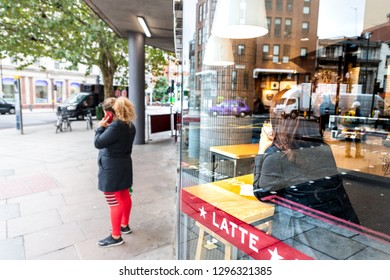 London, UK - September 12, 2018: Neighborhood of Pimlico Victoria with woman standing on sidewalk by Pret A Manger modern cafe restaurant window reflection