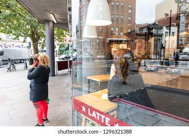London, UK - September 12, 2018: Neighborhood of Pimlico Victoria with woman standing on sidewalk by Pret A Manger cafe restaurant window reflection