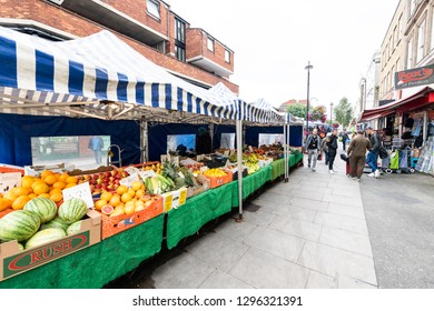 London, UK - September 12, 2018: Neighborhood food market in Pimlico Victoria with people walking on street road by fresh fruit and vegetable tent stands