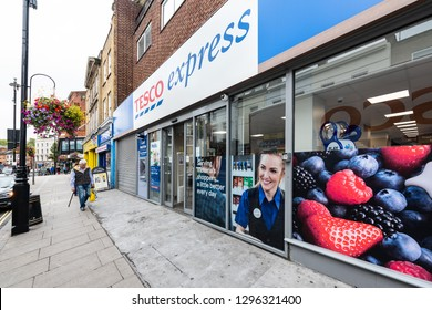 London, UK - September 12, 2018: Neighborhood local store Tesco Express blue grocery shopping storefront facade exterior entrance with sign and people walking in Pimlico
