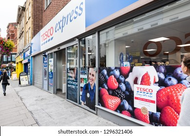 London, UK - September 12, 2018: Neighborhood local store Tesco Express grocery shopping storefront facade exterior entrance with sign and people walking in Pimlico
