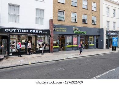 London, UK - September 12, 2018: Neighborhood local store little Waitrose upscale expensive green sign grocery shopping storefront facade exterior entrance with people on sidewalk in Pimlico