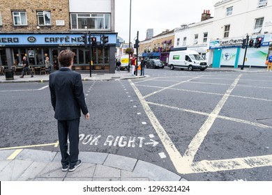 London, UK - September 12, 2018: Neighborhood of Pimlico with road and cafe Nero restaurant and one young business man people waiting to cross street