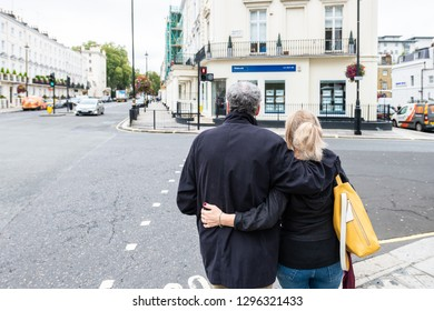 London, UK - September 12, 2018: Romantic couple embracing standing in neighborhood district of Pimlico Victoria street alley with historic architecture waiting to cross street