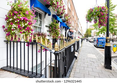 London, UK - September 12, 2018: View of neighborhood of Pimlico street sidewalk with historic Best Western hotel architecture, people with many colorful flower decorations