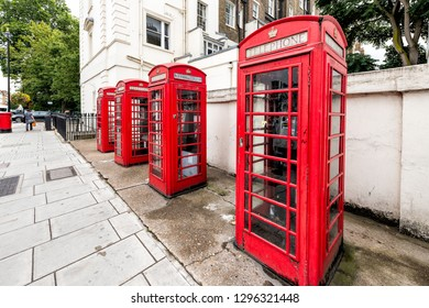 London, UK - September 12, 2018: Pimlico or Victoria in Westminster with typical architecture street road and four vibrant red telephone booth box during day