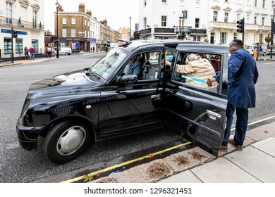 London, UK - September 12, 2018: Pimlico or Victoria street road with historic architecture and man helping woman get into black taxi cab