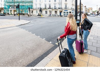 London, UK - September 12, 2018: View of neighborhood of Pimlico street road with historic architecture and people girls with luggage waiting to cross street