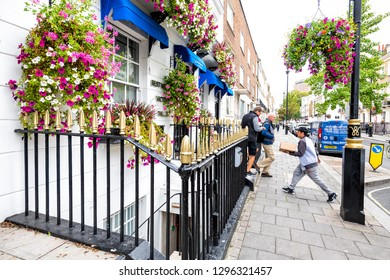 London, UK - September 12, 2018: View of neighborhood of Pimlico street sidewalk with historic architecture and people walking with many colorful flower decorations