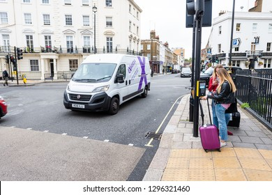London, UK - September 12, 2018: View of neighborhood district of Pimlico street alley with historic architecture and people with luggage waiting to cross street