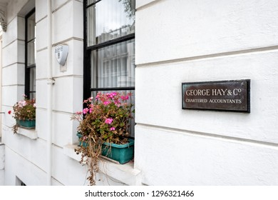 London, UK - September 12, 2018: Neighborhood district of Pimlico street with historic architecture and closeup of sign for George Hay and Company Accountants