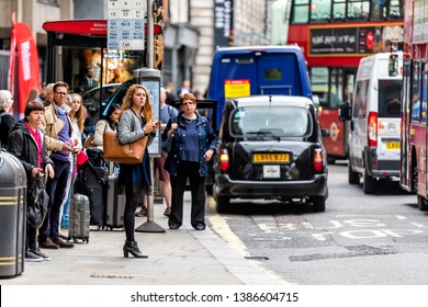 London, UK - September 12, 2018: Bus stop on street road in Aldwych with people young woman waiting in city downtown busy traffic