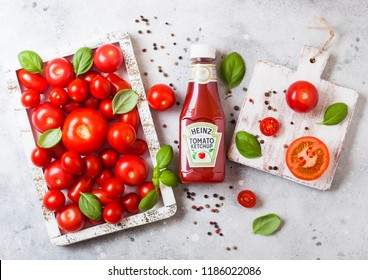 LONDON, UK - SEPTEMBER 13, 2018: Heinz ketchup with fresh raw tomatoes in box on stone background.