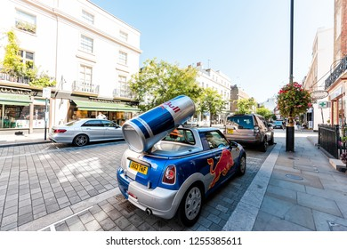 London, UK - September 13, 2018: Neighborhood district of Belgravia with street, car and sign for red bull energy drink parked on road