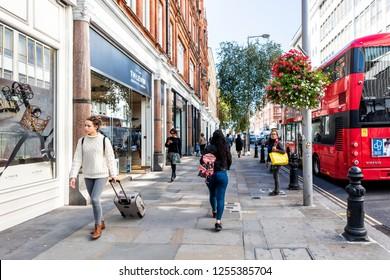 London, UK - September 13, 2018: Neighborhood district of Chelsea, street, red double decker bus, TM Lewin retail store, people walking on sidewalk