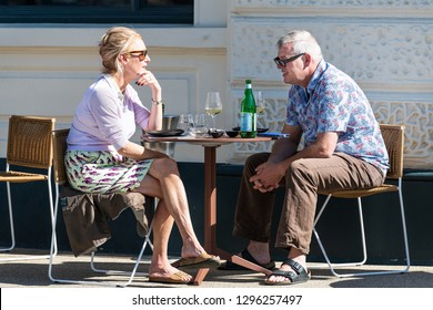 London, UK - September 13, 2018: Senior ouple man and woman sitting at table at cafe outdoor seat chairs talking and drinking wine eating in Pimlico