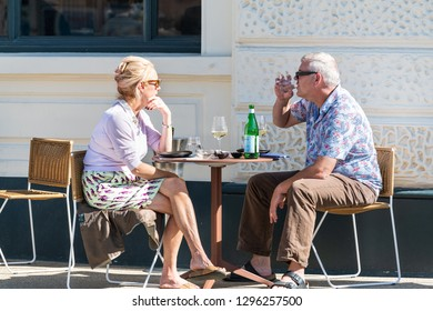 London, UK - September 13, 2018: Senior ouple man and woman sitting at table at cafe outdoor seat chairs talking and drinking wine in Pimlico